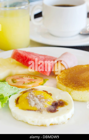 full meal for breakfast ( pancake , fried egg , ham and sausage , fresh vegetable and fruits , hot coffee and juice - Stock Photo