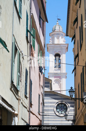 Bell tower of St Maria church seen along a narrow street within the historic northern Italian town of Albenga. - Stock Photo