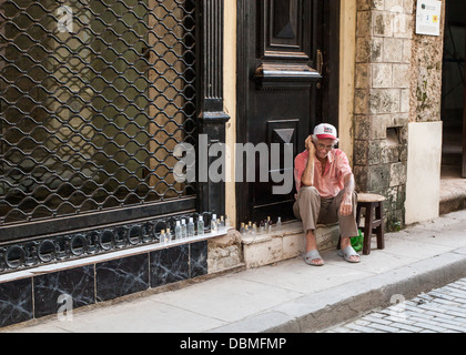 Old man in Havana sat on the door step collection bottles for tourists - Stock Photo