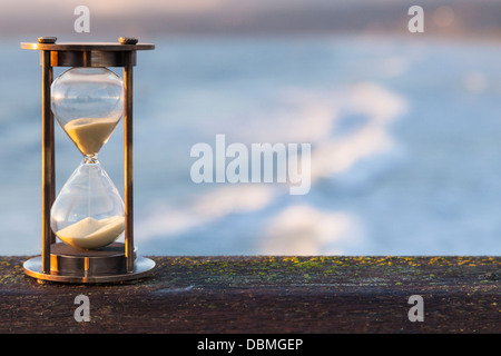 Hourglass Outdoors - sunlit hourglass or sand timer with a background of flowing water. - Stock Photo