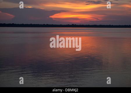 Orange calm sunset on the Rio Negro in the Amazon River basin Brazil. - Stock Photo