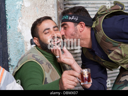 Aleppo, Syria: A Free Syrian Army rebel kisses another in Karm AL Jabal. - Stock Photo