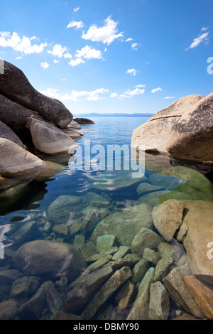 Large, smooth granite boulders define a beautiful shoreline of pristine lake Tahoe with clear, calm water. - Stock Photo