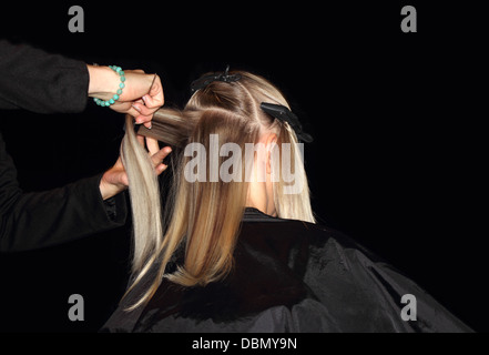 Blonde young woman in hair salon - Stock Photo