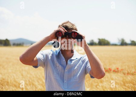 Man On Field Looking Through Binoculars, Croatia, Dalmatia, Europe - Stock Photo