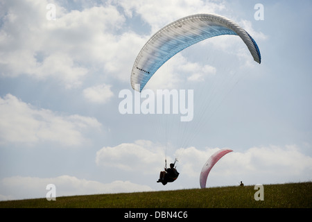 Paraglider against blue sky and fluffy clouds with space for text on left hand side of frame - Stock Photo