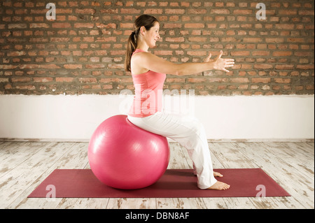 Woman Doing Pilates With Fitness Ball, Munich, Bavaria, Germany, Europe - Stock Photo
