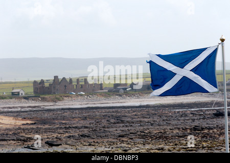 A Scottish flag flying on Orkney with the ruins of the Earl's Palace at Birsay in the background - Stock Photo