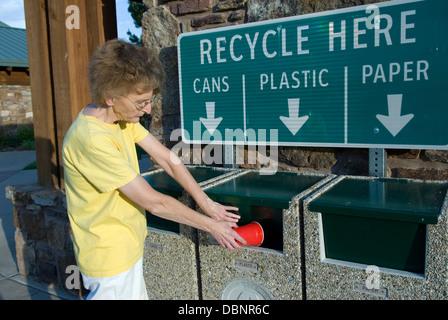 Caucasian woman throwing plastic cup into recycling bin, USA. - Stock Photo
