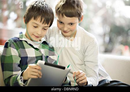 Two boys using digital tablet, Osijek, Croatia, Europe - Stock Photo