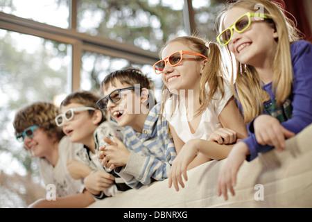 Children watching television wearing 3D glasses, Osijek, Croatia, Europe - Stock Photo