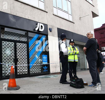 Police stand in front of a JD sports store damaged after a night of rioting and looting in Camden Town, London, - Stock Photo