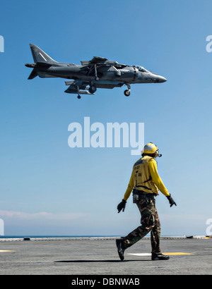 A US Navy Aviation Boatswain Mate watches a AV-8B II Harrier fighter jet land on the flight deck of the amphibious - Stock Photo