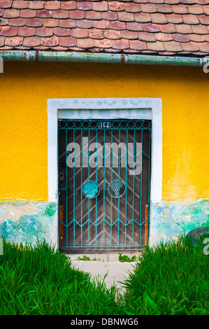 Old rusty door on yellow wall - Stock Photo