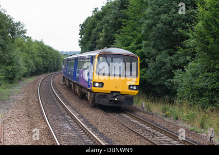 A diesel passenger train on the mainline approaching Deighton station near Huddersfield, West Yorkshire, England - Stock Photo