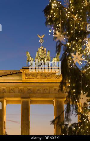 Illuminated Christmas tree and Brandenburg Gate on square Pariser Platz in Berlin in the evening, close up, detail - Stock Photo