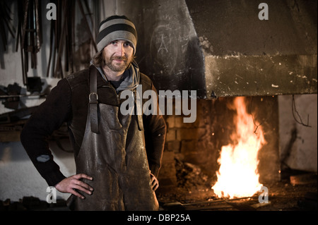 Blacksmith standing in workshop, forge in background, Landshut, Bavaria, Germany - Stock Photo