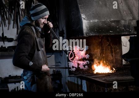 Blacksmith making coat of arms from iron, forge in background, Landshut, Bavaria, Germany - Stock Photo