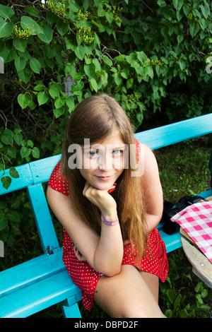 Portrait of girl (14-15) sitting on bench - Stock Photo