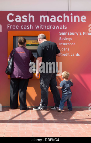 Man woman and child withdrawing money from a cash machine - Stock Photo