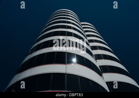 Twin circular white striped office blocks in Wellington New Zealand reflecting sun against deep blue sky - Stock Photo