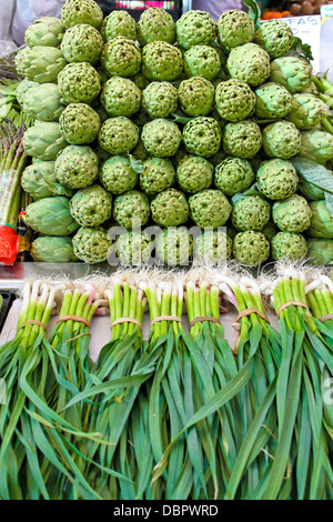 artichoke and young garlic on a Central market in Valencia, Spain - Stock Photo