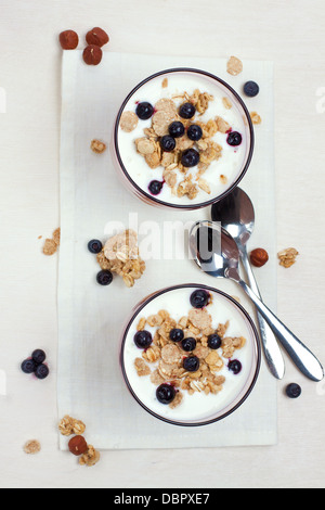yogurt with muesli and berries in glasses from above - Stock Photo
