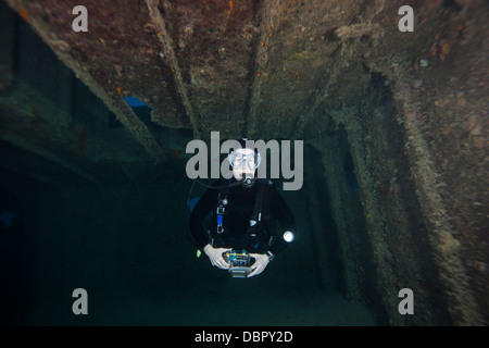 Scuba diver inside the Prince Albert Wreck off the island of Roatan, Honduras. - Stock Photo