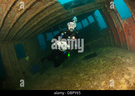Scuba diver inside the wreck of the Mr. Bud, a former shrimping boat, scuttled off the island of Roatan, Honduras - Stock Photo