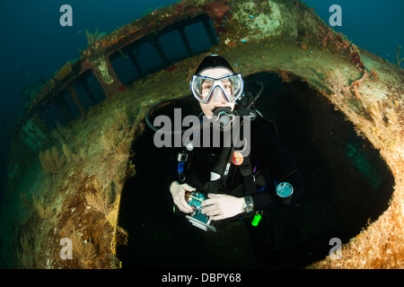 Scuba diver emerging from the wreck of the Mr. Bud, a former shrimping boat, scuttled off the island of Roatan, - Stock Photo