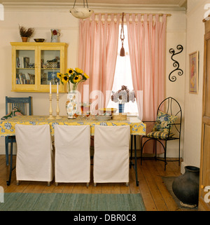 White Loose Covers On Chairs At Table With Yellow Cloth In Economy Style Dining