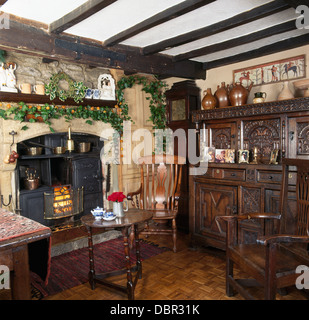 Ivy Christmas garland above old range in country dining room with Jacobean-style carved wood dresser and chair - Stock Photo