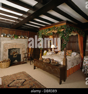 Fourposter bed decorated for Christmas with garland of ivy in beamed country bedroom with oak chest and stone fireplace - Stock Photo