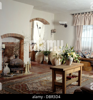 Simple Wooden Table And Patterned Neutral Rug In Cottage Living Room With  Collection Of Tall Pots