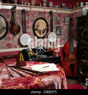 Collection of banjos on walls of small music room with dado rail and table with patterned red velvet cloth and double - Stock Photo