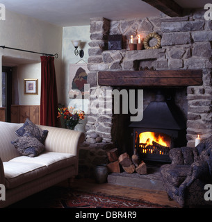Cottage Living Room With Fireplace lighted candles fireplace with wood-burning stove in cottage