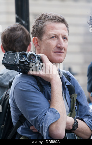 Photographer holding a twin lens rolleiflex camera at G20 Summit Protest outside Bank of England, London, UK - Stock Photo