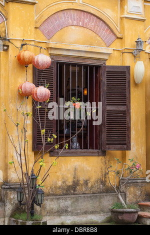Facade of colonial-style building with silk lanterns and wooden shutters in Old Quarter, Hoi An, Vietnam, Southeast Asia