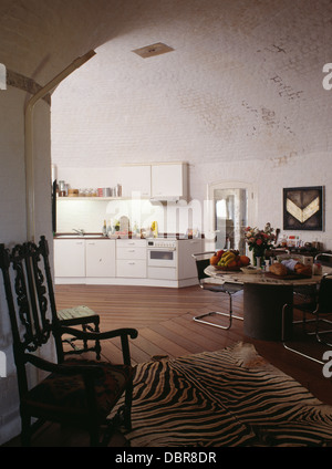 Jacobean chair and old zebra-skin rug in dining area of modern high-ceilinged kitchen in converted Martello Tower - Stock Photo