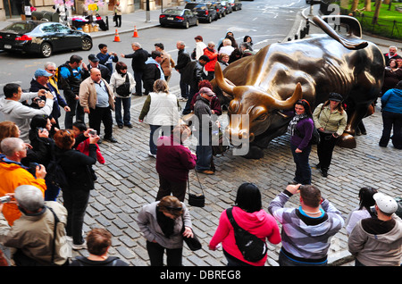 Tourists visits the Wall Street Charging Bull in Manhattan NYC , USA. - Stock Photo