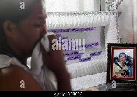 General Santos city, Southern Philippines. 3rd August, 2013. Mario Sy's Wife Violeta Sy mourn inside trier house - Stock Photo