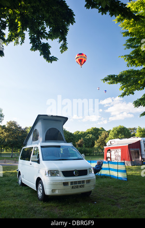 A brightly coloured hot air balloons flying above a campsite with and a VW camper van pitched up on a peaceful summer - Stock Photo