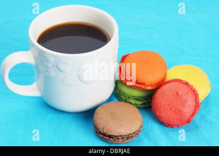 Cup of black coffee and colorful macarons on blue - Stock Photo