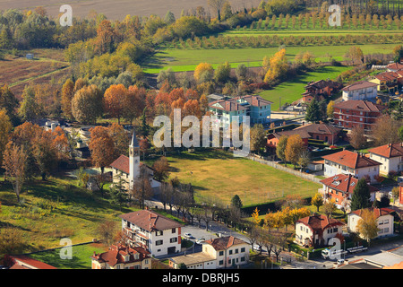 Aerial view on small town among beautiful colorful fields and trees in autumn in Piedmont, Northern Italy. - Stock Photo
