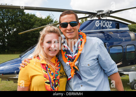 Biggin Hill,UK,3rd August 2013, Bear Grylls poses with a female scout in front of a helicopter after his visit to - Stock Photo