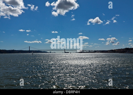 View on the river Tagus with the famous bridge Ponte de 25 de Abril in the distance, Lisbon, Portugal. - Stock Photo