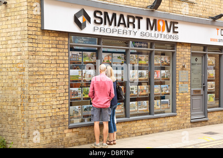 Couple looking at properties for sale or rent at an estate agent shop window, Peterborough, England - Stock Photo