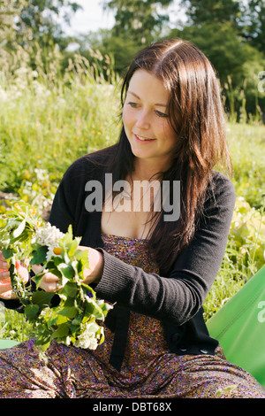 Young woman making flowery wreath - Stock Photo