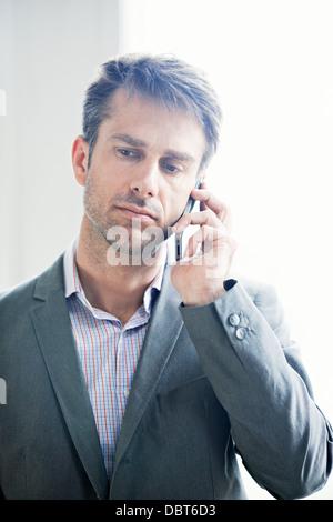 Mature businessman using mobile phone - Stock Photo