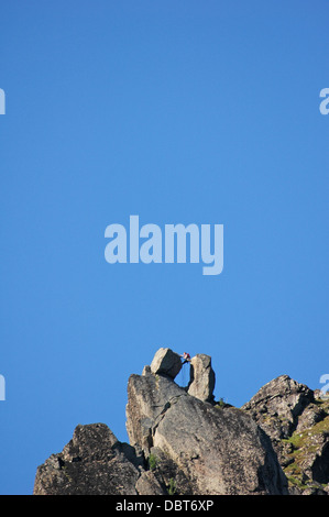Climbing mountaineer on top of 'Svolvær Goat' in Svolvær, Lofoten, Norway - Stock Photo